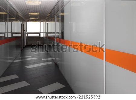 Long hallway in the modern corporate office building with glass walls - stock photo