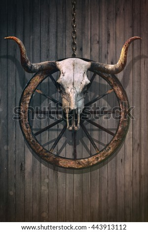Long horned bull skull and old west wagon wheel hanged on a wooden wall - stock photo