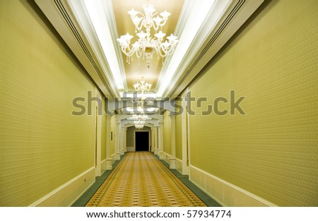 Long hotel corridor with  carpet and green wallpaper - stock photo