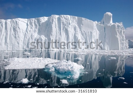 Long iceberg wall seen from a little distance. The Iceberg still has'nt turned around. There are smaller pieces of ice in the foreground. - stock photo