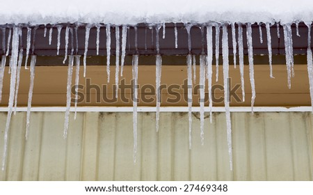 Long icicles hanging from the side of a building. - stock photo