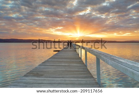 LONG JETTY, AUSTRALIA - AUGUST 3, 2014;  A couple enjoy a beautiful sunset at Long Jetty on the Central Coast Australia - stock photo