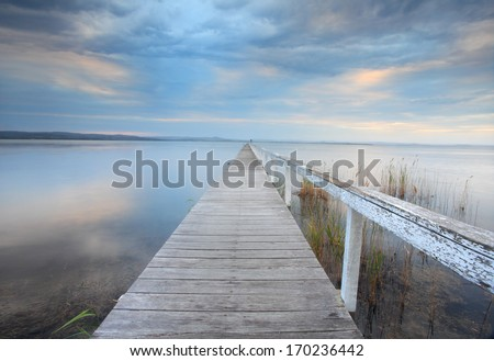 Long Jetty serenity - Alone let him constantly meditate in solitude on that which is salutary for his soul, for he who meditates in solitude attains supreme bliss. - stock photo