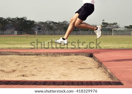 Long jump, half of the body of a 20-year-old Asian woman - stock photo