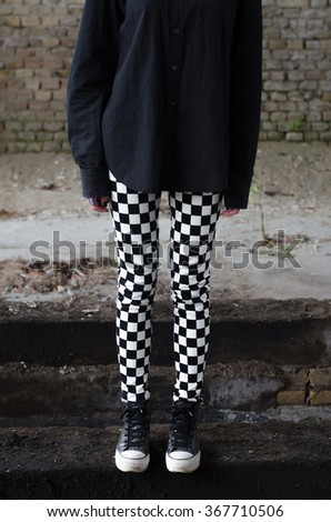 Long legs and sneakers of teenage goth girl standing in abandoned building. - stock photo