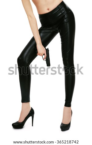 Long legs of slim sexy girl in leather skinny pants and high heels holding a pistol in her hand over white background - stock photo