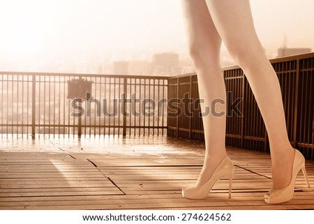 long legs of woman and landscape of city  - stock photo