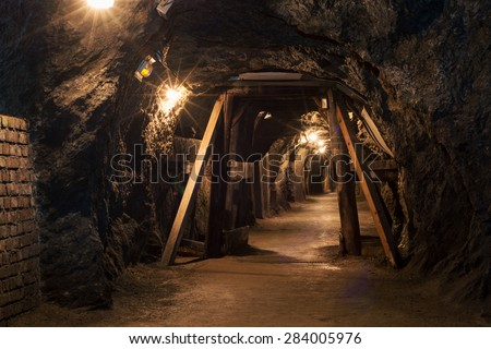 Long lighten tunnel through gypsum mine with wooden beams - stock photo