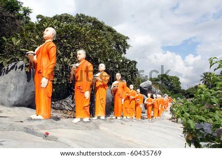 Long line of monks in Dambulla, Sri Lanka - stock photo