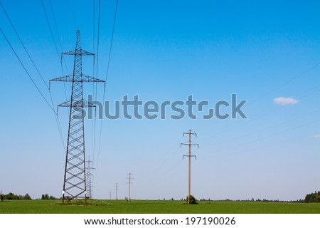 long lines of powerline towers stretching across a beautiful countryside - stock photo