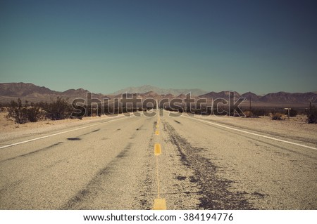 long lonely old asphalt road Route 66 in Arizona and blue sky, USA, Vintage filtered style