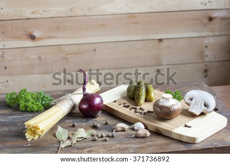 Long noodles linguine, pickled cucumbers gherkins, champignon mushrooms, herbs, spices and vegetables on wooden table - stock photo