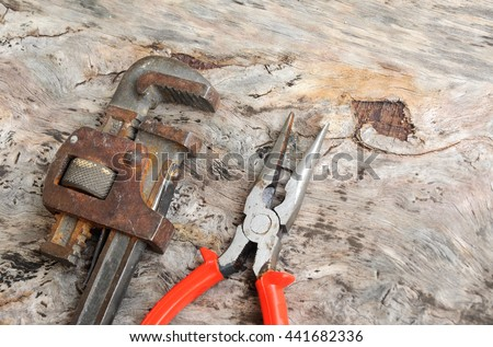 Long nose pliers and adjustable wrench on wood grain background.