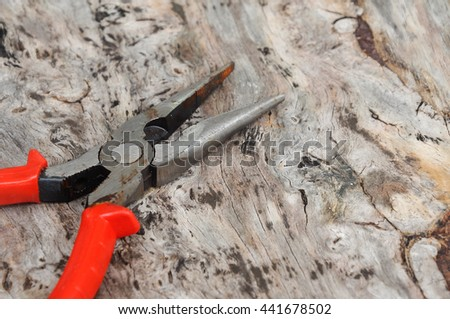 Long nose pliers on wood grain background.  - stock photo