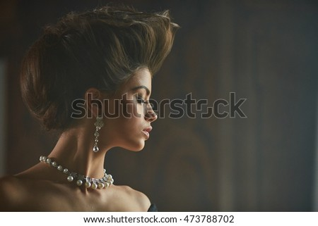 Long pearl earring hangs from an ear of beautiful model with high hair-do
