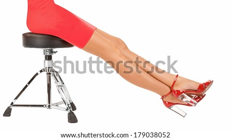 Long perfect female legs wearing high heels red shoes sitting on metal stool isolated on white background - stock photo