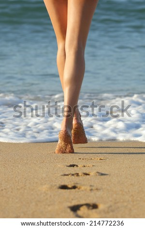 Long perfect woman legs walking on the sand of the beach towards the sea leaving footprints - stock photo