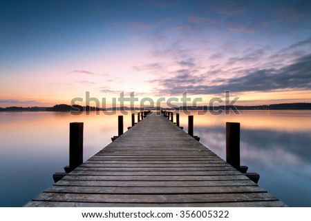 long pier leading out onto the lake, sunrise on lake, long way out