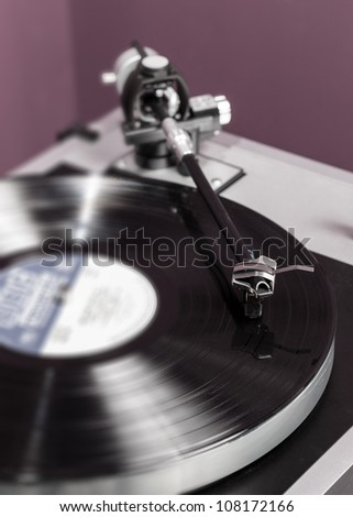 Long Playing record LP on retro record player with tone arm and cartridge - stock photo