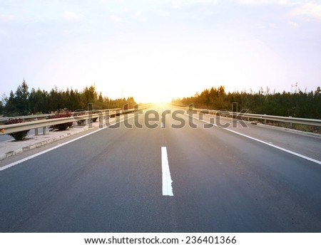 Long road at sunset - stock photo