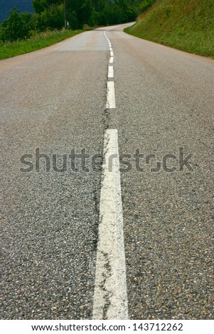 Long road traveling up in the mountains - stock photo