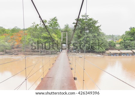long rope  or string bridge across the river in village at Thailand countryside, folk way across waterfall, rope or string bridge at Kheck River with trees at riverside view - stock photo