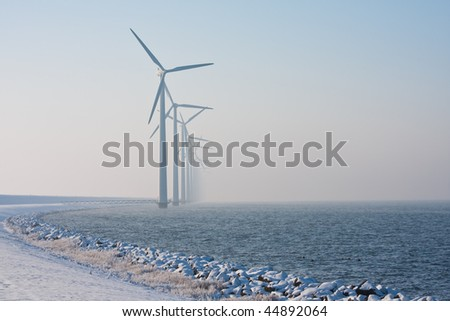 Long row of Dutch windmills disappearing in winter haze