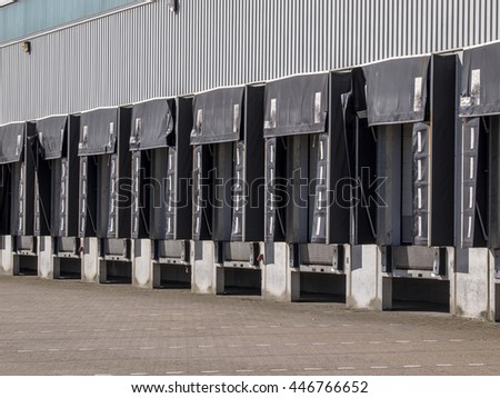 Long row of Empty Loading Dock Cargo Doors as a concept for Economic Growth - stock photo