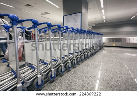 Long row of luggage trolleys at airport terminal - stock photo
