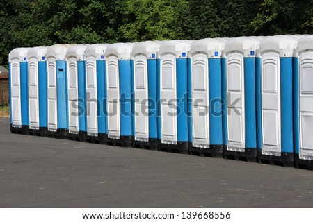 Long row of mobile toilets - stock photo