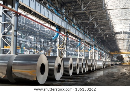 Long row of rolls of aluminum in production shop of plant. - stock photo