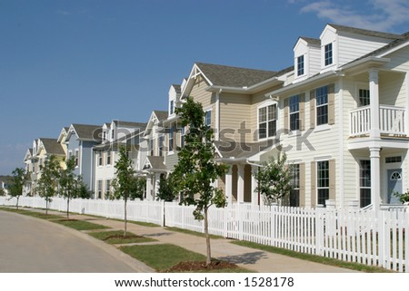 Long row of suburban townhouses with a white picket fence in front.