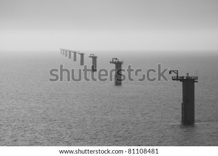 Long row of wind turbine foundations at an offshore windfarm under construction off the Norfolk Coast, North Sea - stock photo