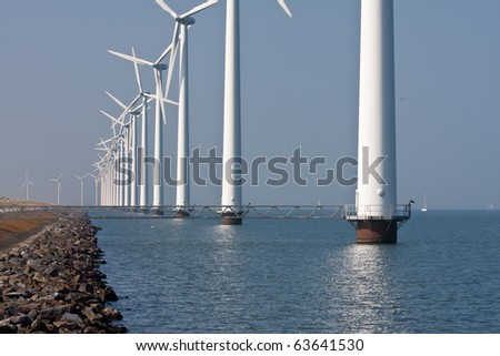 Long row of windmills standing in Dutch sea - stock photo