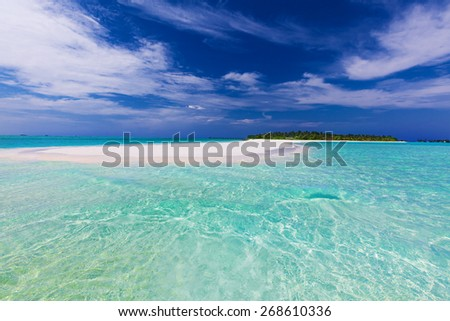 Long sand bar at the end of tropical island with pristine water - stock photo