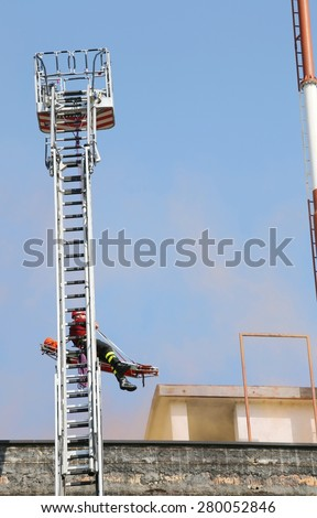 long scale of firefighters for the recovery of wounded during the fire - stock photo