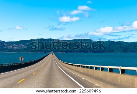 Long scenic road bridge with several lanes with raised sections and fencing in wide mouth of the Columbia River in Astoria, Pacific, rests on the horizon on the opposite bank of the hilly with trees. - stock photo