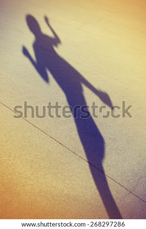 Long shadow of a kid playing in the street, artistic abstract photo with selective focus toned with a retro vintage instagram filter  - stock photo