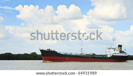 Long ship on a river with beautiful sky - stock photo