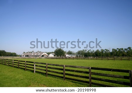 Long shot of a white multi-stall horse barn surrounded by green pastures and brown plank fences. Farm is framed against a clear blue sky.  PHOTOID: Willingham-00013 - stock photo