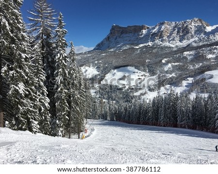 Long ski slopes. Red track with a blue sky and mighty mountains on the background. - stock photo