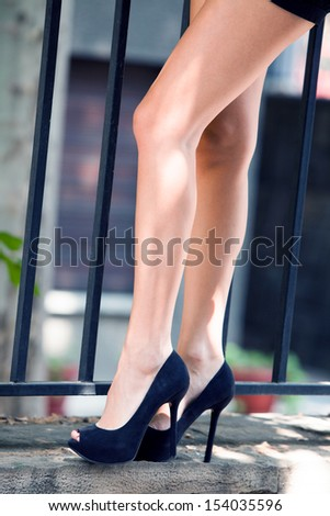 long slim woman legs in black high heel shoes by fence outdoor shot in the city - stock photo