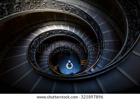 Long spiral, winding stairs. Dark shadows, mysterious mood with single soft light. - stock photo