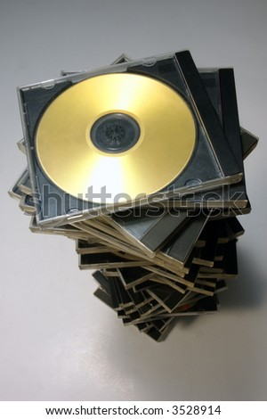 Long stack of classic CD/DVD case with golden disc from above - stock photo