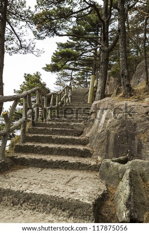 Long staircase going upward into Yellow Mountain park with trees and sky in background - stock photo