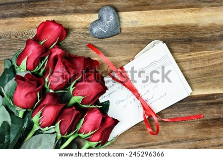 Long stem red roses with a stack of old letters tied with a red ribbon and card a little stone heart with the word love. - stock photo