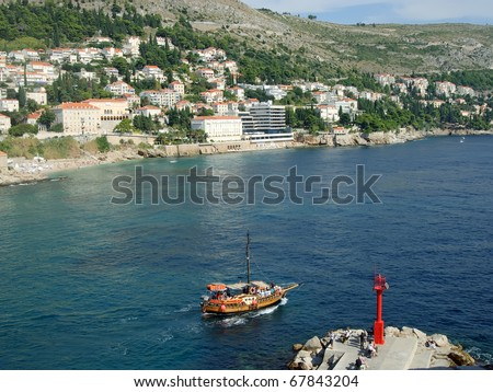 Long stone mole with red lighthouse in Dubrovnik - stock photo