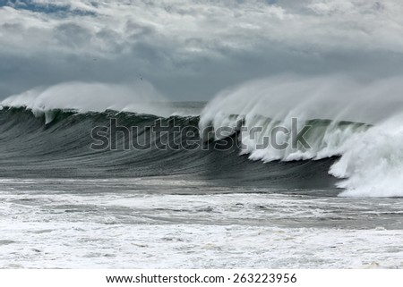 Long stormy waves approaching the Portuguese coast. Enhanced sky. - stock photo
