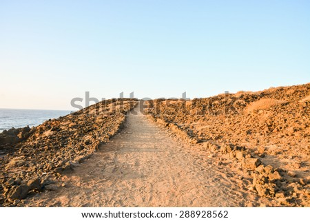 Long Straight Dirt Desert Road disappears into the Horizon. - stock photo