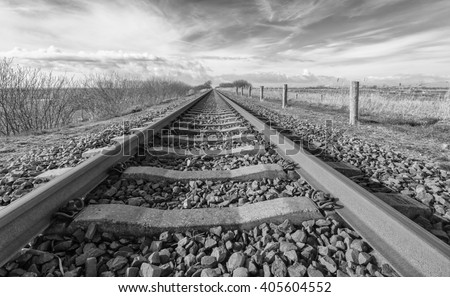 Long straight railroad from rusty rails on concrete sleepers in a rural area in the Netherlands. - stock photo